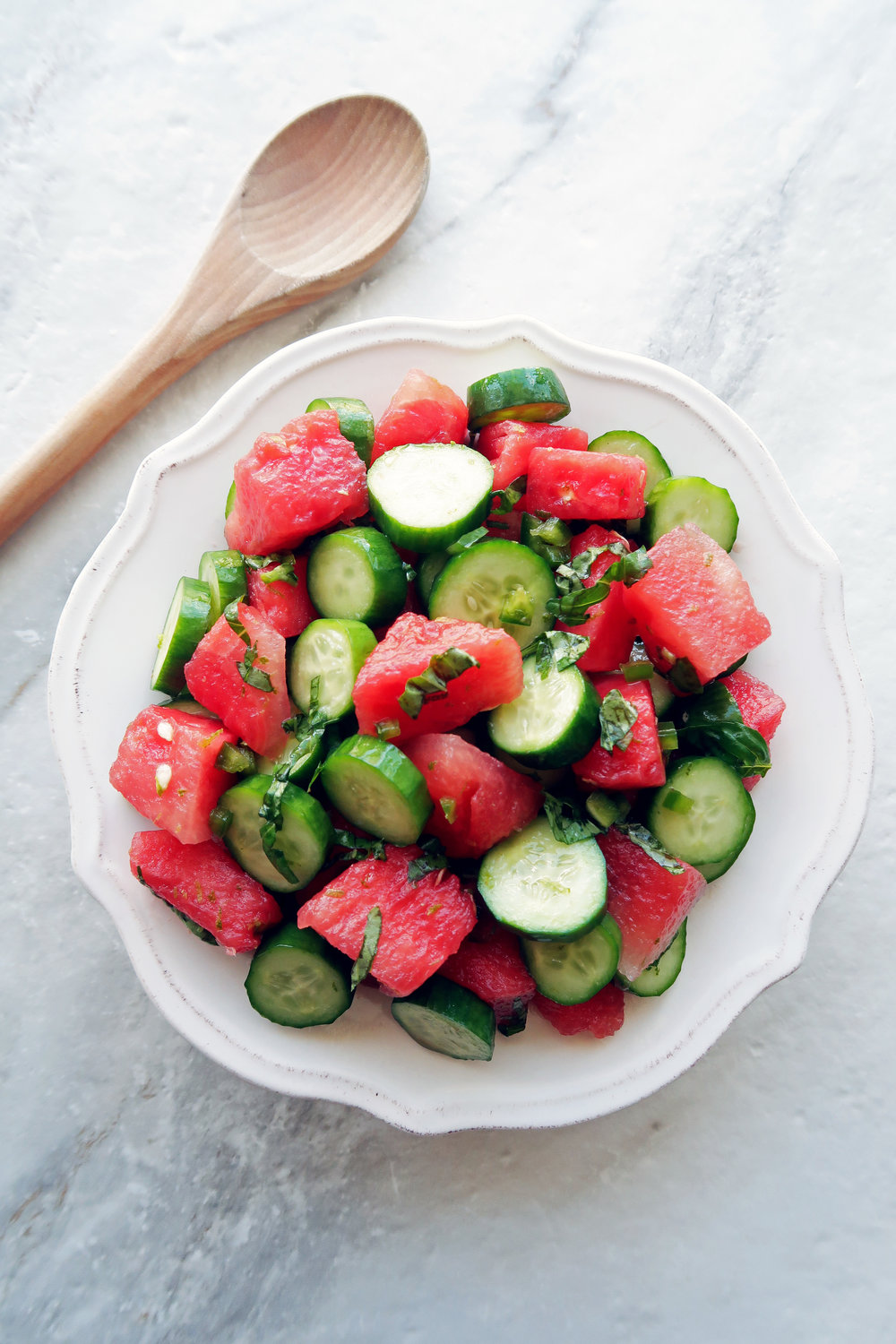 Watermelon Cucumber Jalapeno Salad on a white plate with a wooden spoon on the side of the plate.