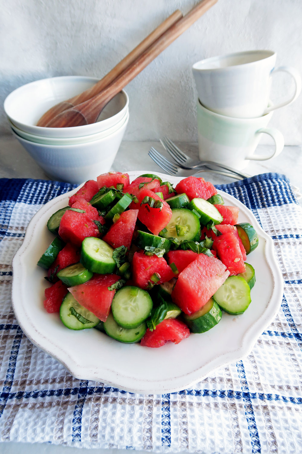 Watermelon Cucumber Jalapeno Salad on a white plate with three bowls, two wooden spoons, two forks, and two cups in the background.