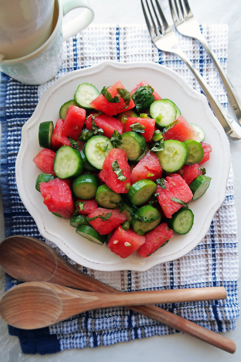 Watermelon Cucumber Jalapeno Salad piled on a white plate with two wooden spoons and two forks around the plate.