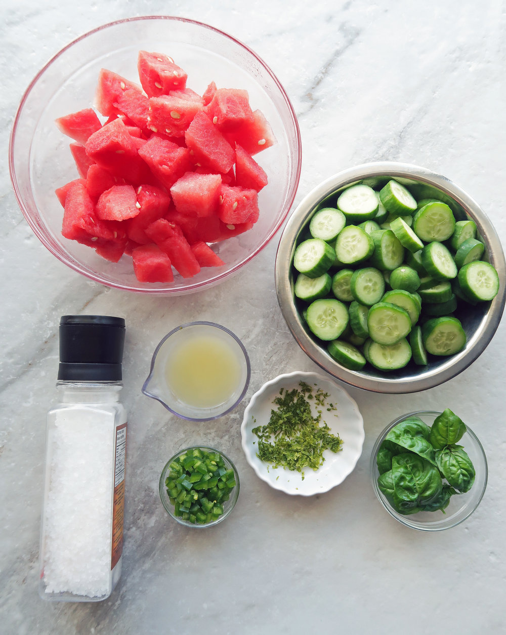 Bowls containing chopped watermelon, cucumber, and jalapeno along with lime zest, lime juice, and basil leaves.