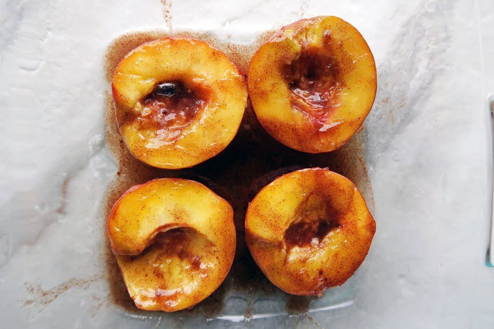 Four peach halves face up in a baking dish and covered with honey, cinnamon, and butter.