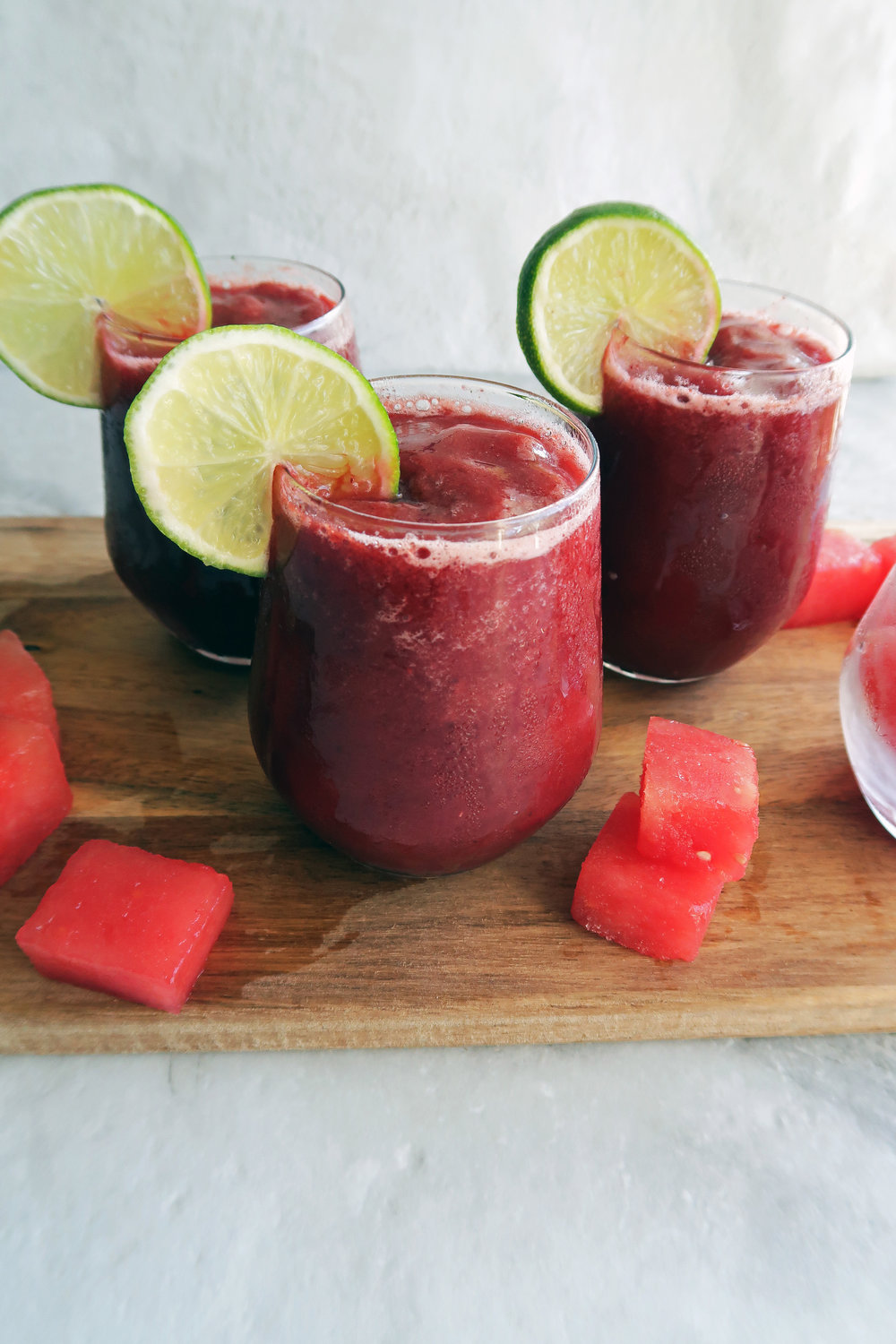 Three 4-Ingredient Watermelon Cherry Slushies in glasses, a lime slice on each glass rim, with watermelon cubes around it.