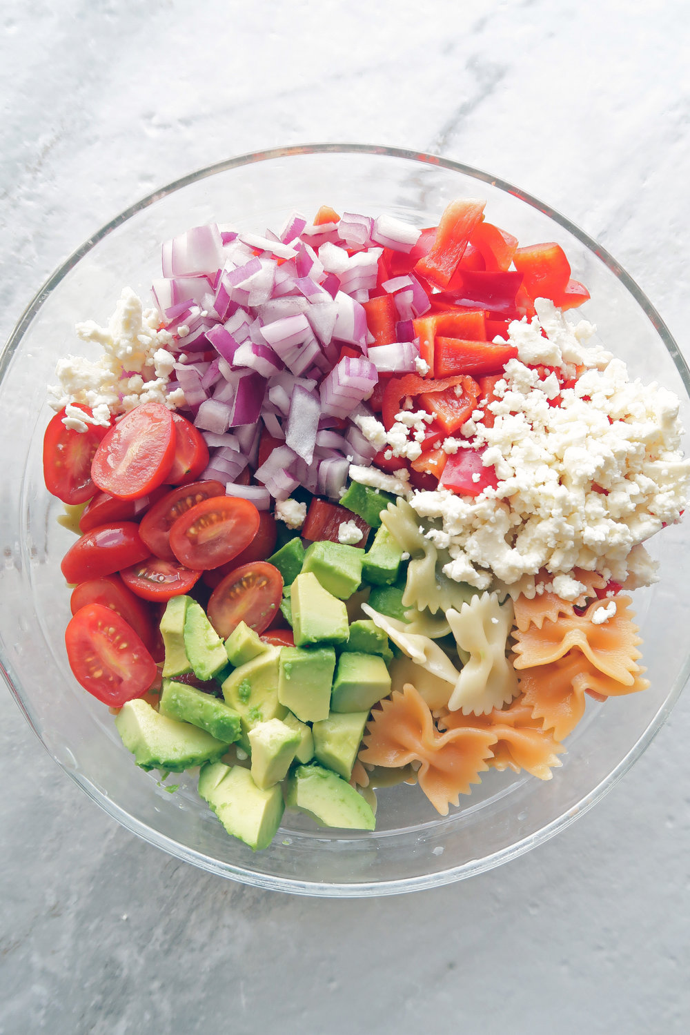 Chopped avocado, tomatoes, red onions, bell pepper, feta, and farfalle pasta in a large bowl.
