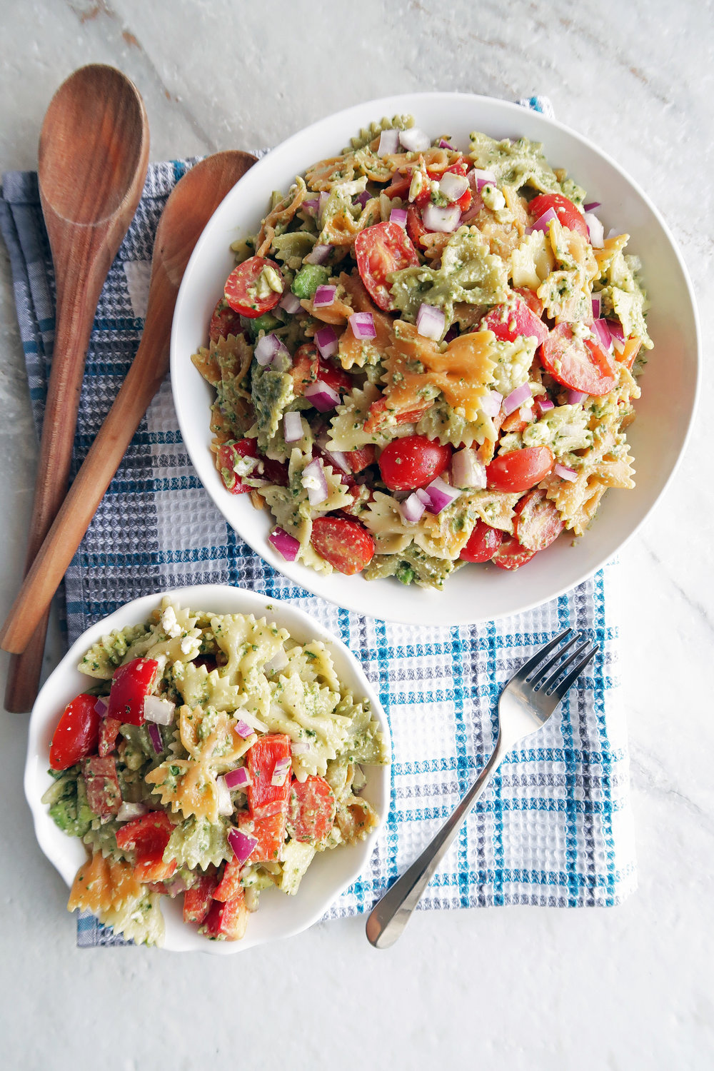 Basil avocado pesto vegetable pasta salad in a large bowl and a small bowl.