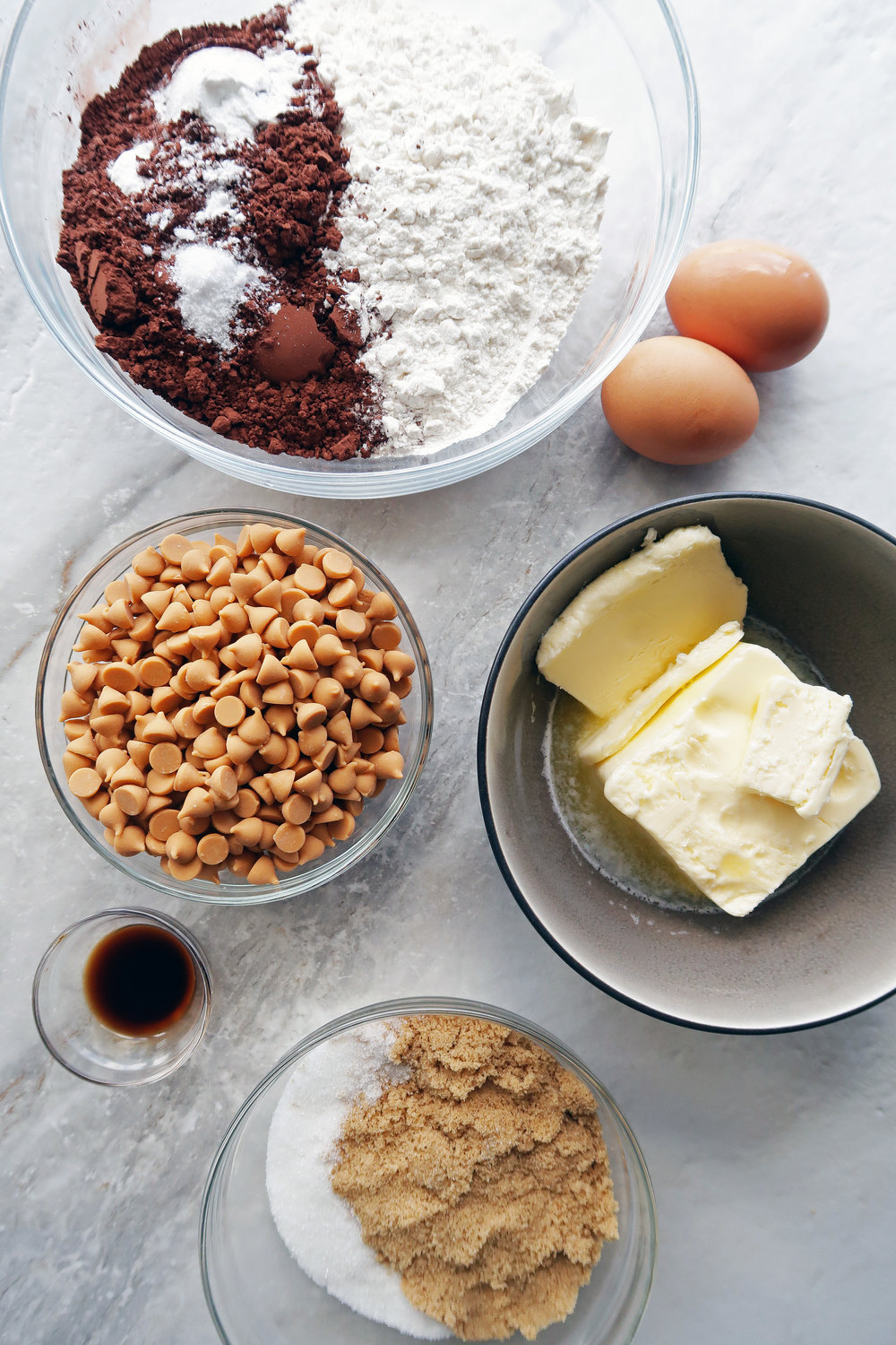Many bowls filled with cocoa powder, flour mixture, sugar, butterscotch chips, eggs, butter, and vanilla.