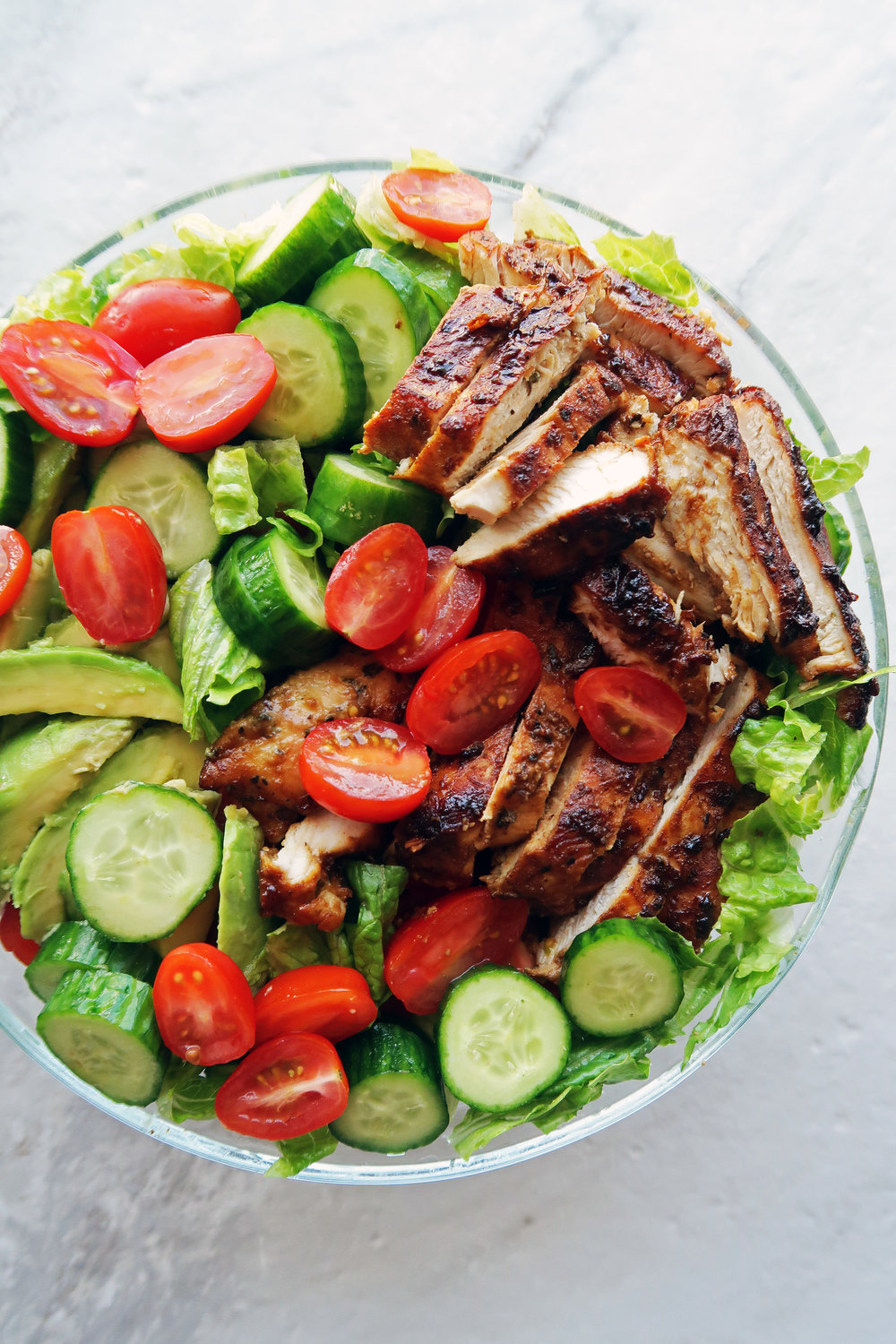 Chopped lettuce, tomatoes, cucumbers, avocado, and sliced honey mustard chicken breasts in a large bowl.