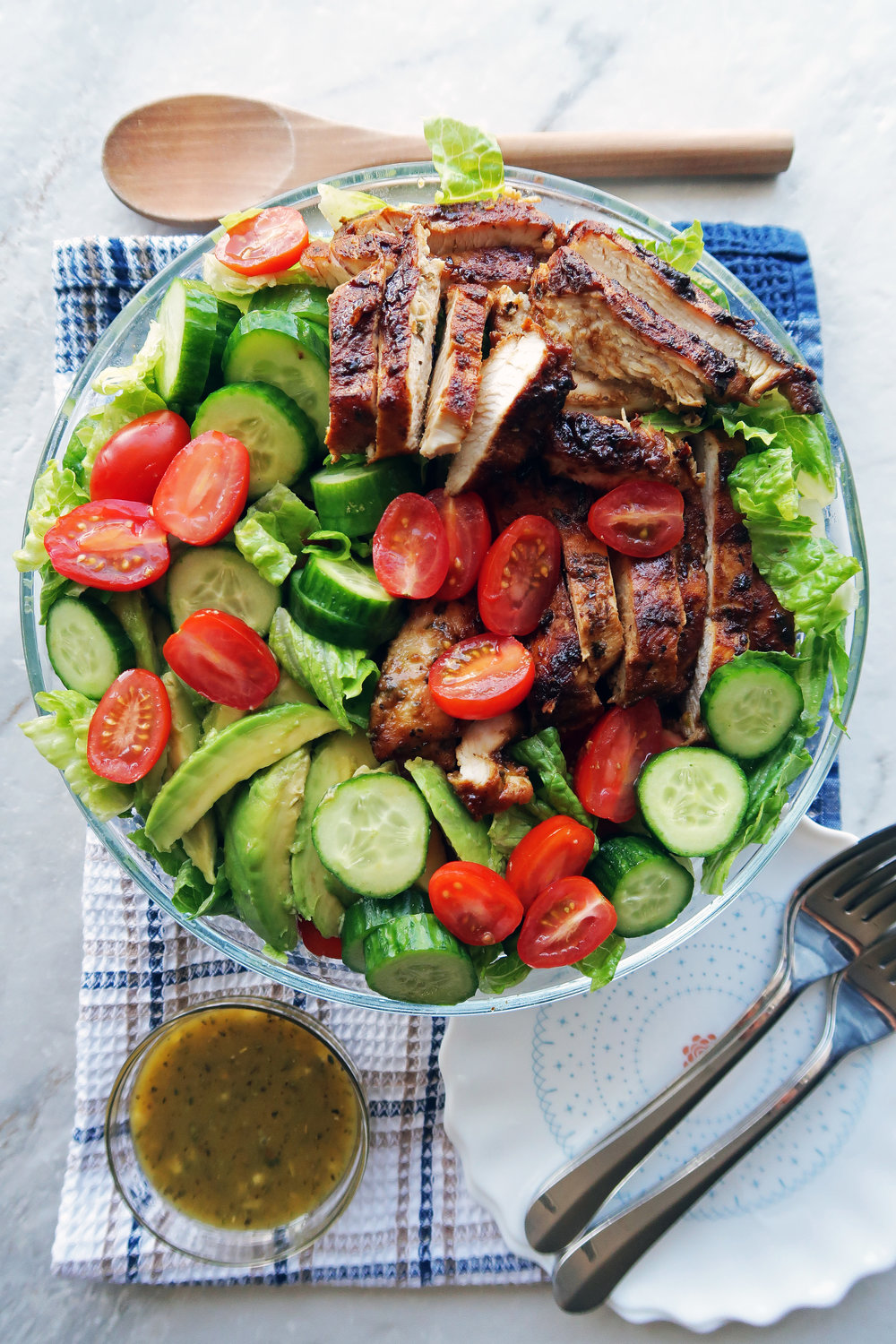 Lettuce, tomatoes, cucumbers, avocado, and sliced honey mustard chicken in a large bowl with dressing on the side.