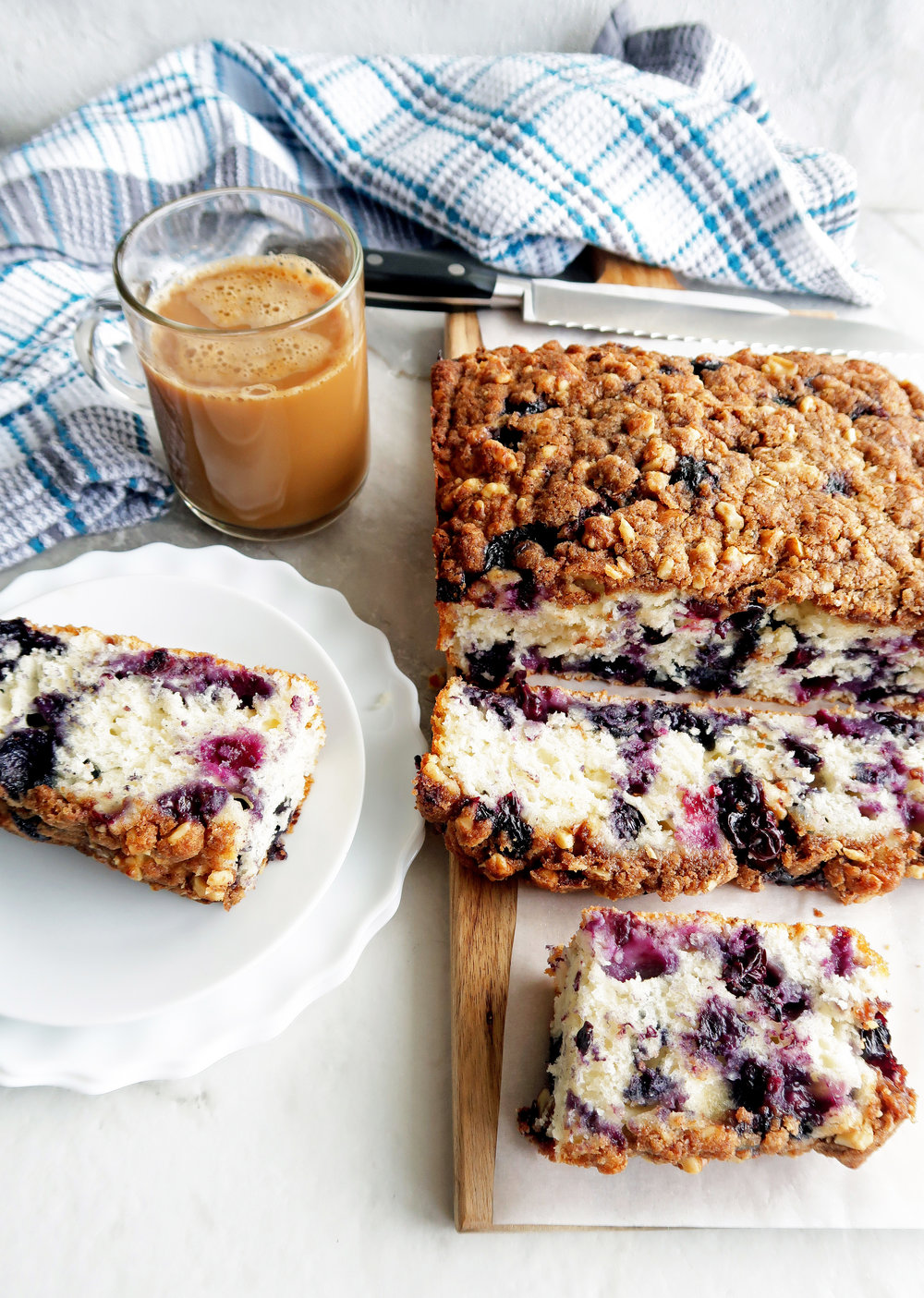 Blueberry coffee cake with brown sugar-walnut crumble on a long wooden board and plate.