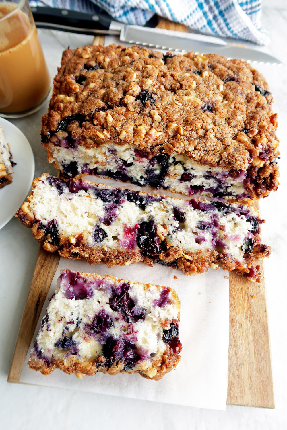 Sliced blueberry coffee cake with brown sugar-walnut crumble on a long wooden board.
