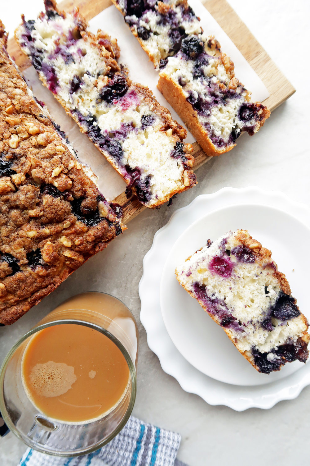 Blueberry coffee cake with crumble on a wooden board and a slice on a white plate.