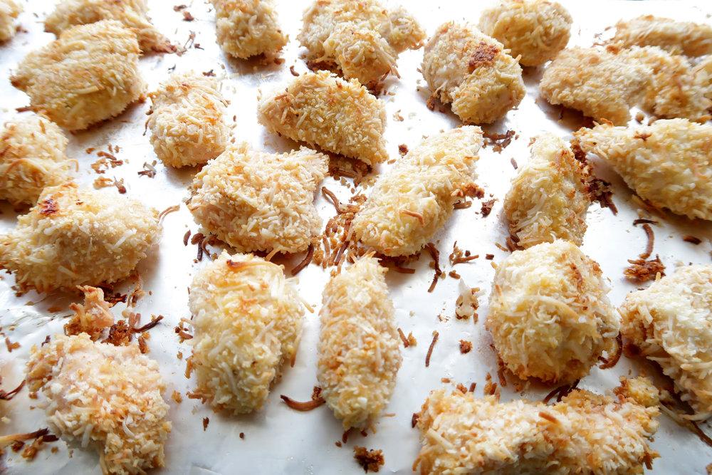 Baked crispy coconut chicken nuggets bites on an aluminum foil lined baking sheet.