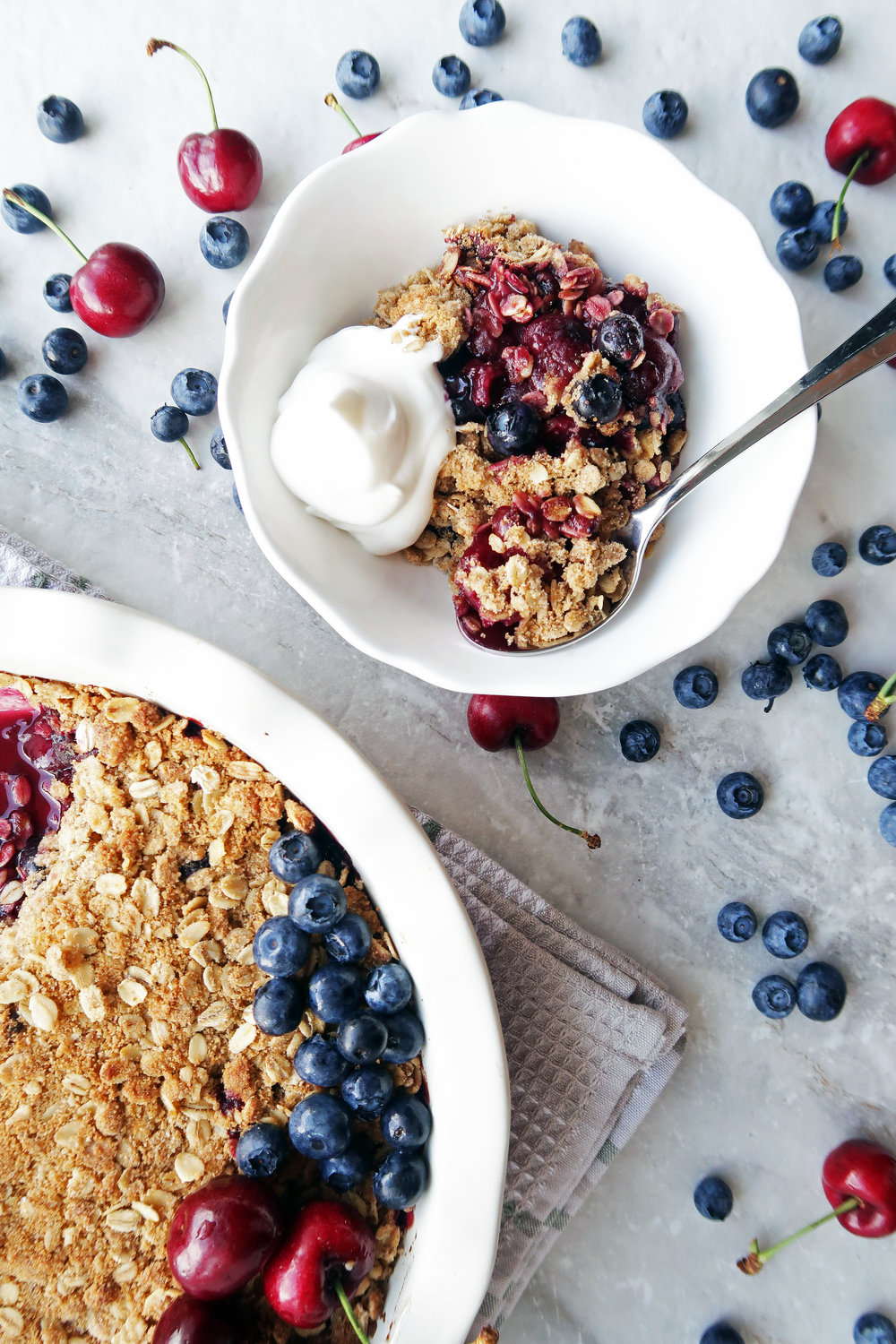 Cherry blueberry oat crisp with whipped cream in a white bowl with a spoon and a large pie dish of oat crisp.