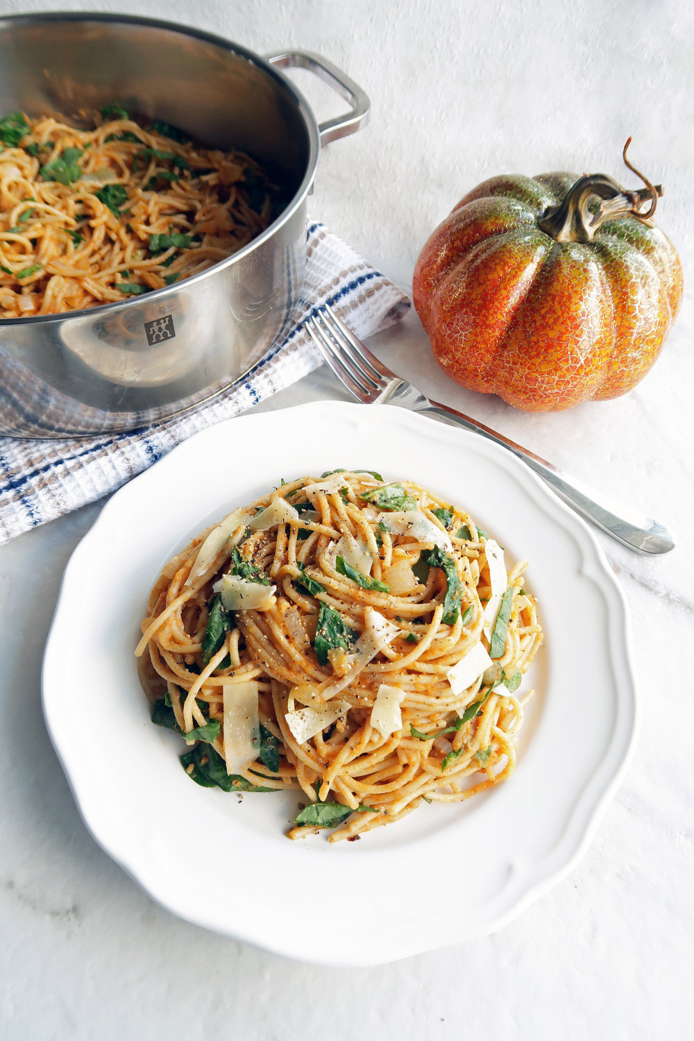 Spaghetti with creamy pumpkin sauce on white plate with more spaghetti in a metal pot in the background.
