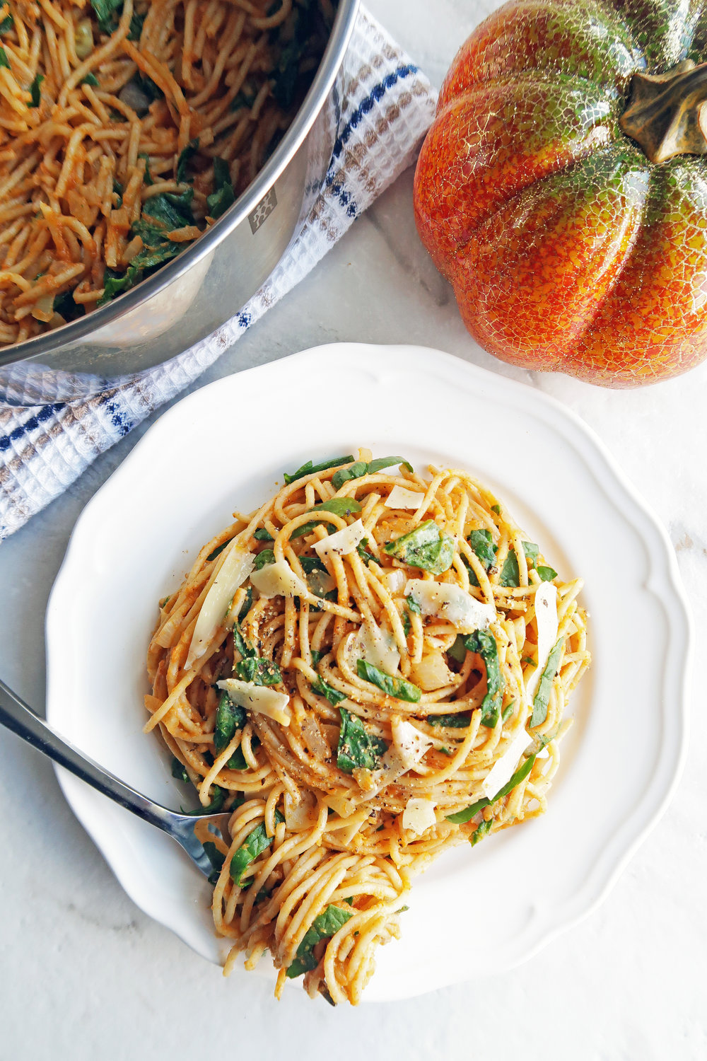 Spaghetti with creamy pumpkin sauce on white plate with more spaghetti in a metal pot behind the plate.