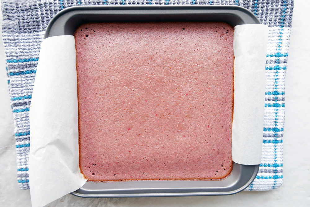 Soft and spongy strawberry layer baked on top of shortbread in a parchment-paper lined baking pan.