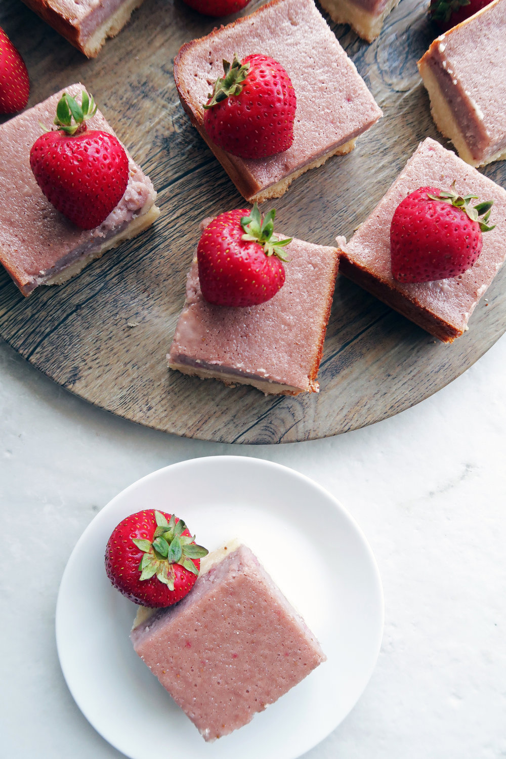 Pink strawberry shortbread bars on a round wooden platter and on a small white plate.