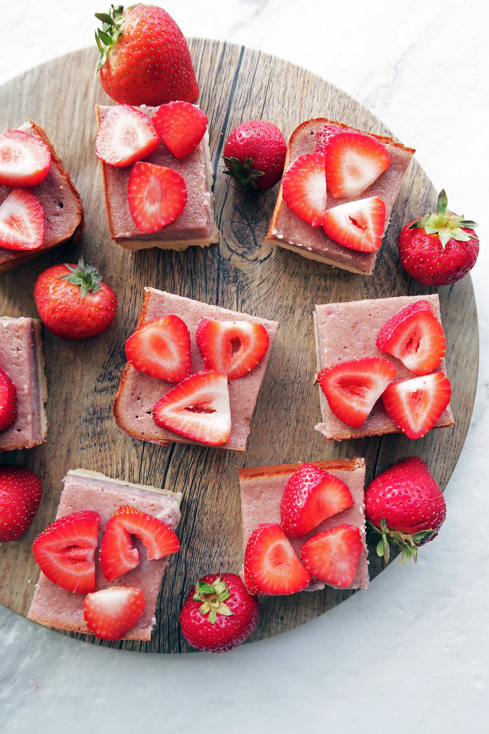 Overhead view of strawberry shortboard bars with fresh strawberry slices on top on a round wooden platter.
