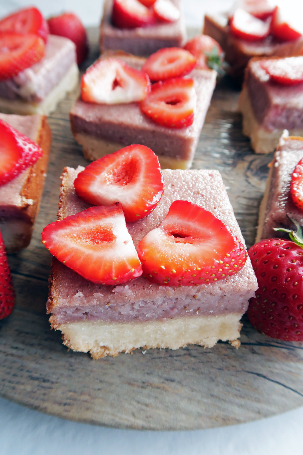 Closeup side angled view of a strawberry shortbread bar with strawberry slices on top -more in the background.