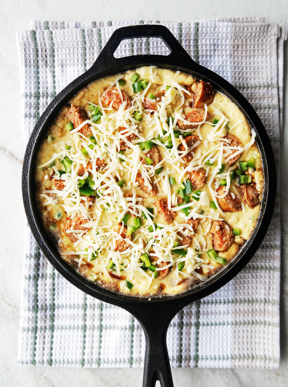 Jalapeño maple and sausage cornbread batter spread on a cast-iron skillet topped with cheese.