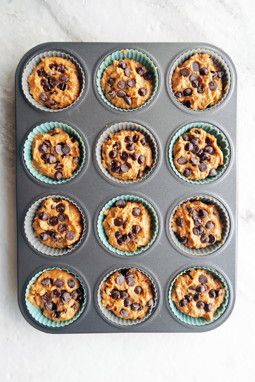 Pumpkin chocolate chip whole wheat muffin batter scooped evenly into a 12 cup muffin pan.