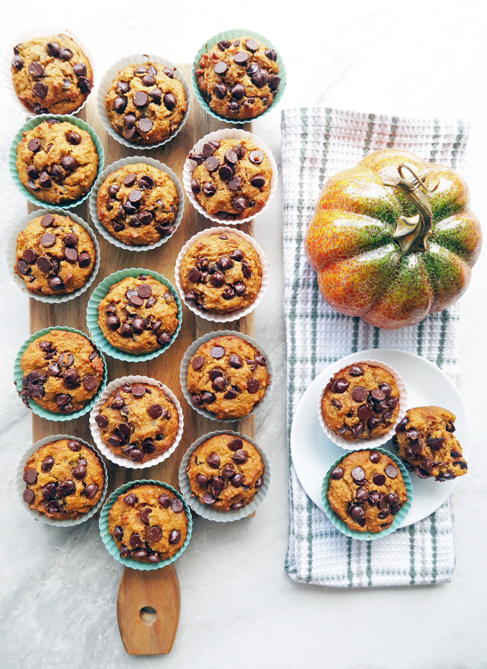 Pumpkin chocolate chip whole wheat muffins placed on a rectangular wooden board and on a white plate.