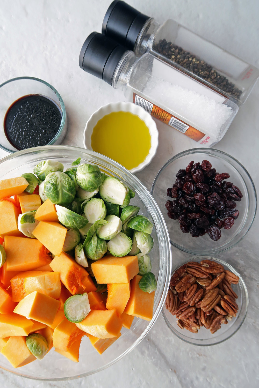 Chopped butternut squash, Brussels sprouts, pecans, dried cherries, balsamic vinegar, and oil in individual bowls.