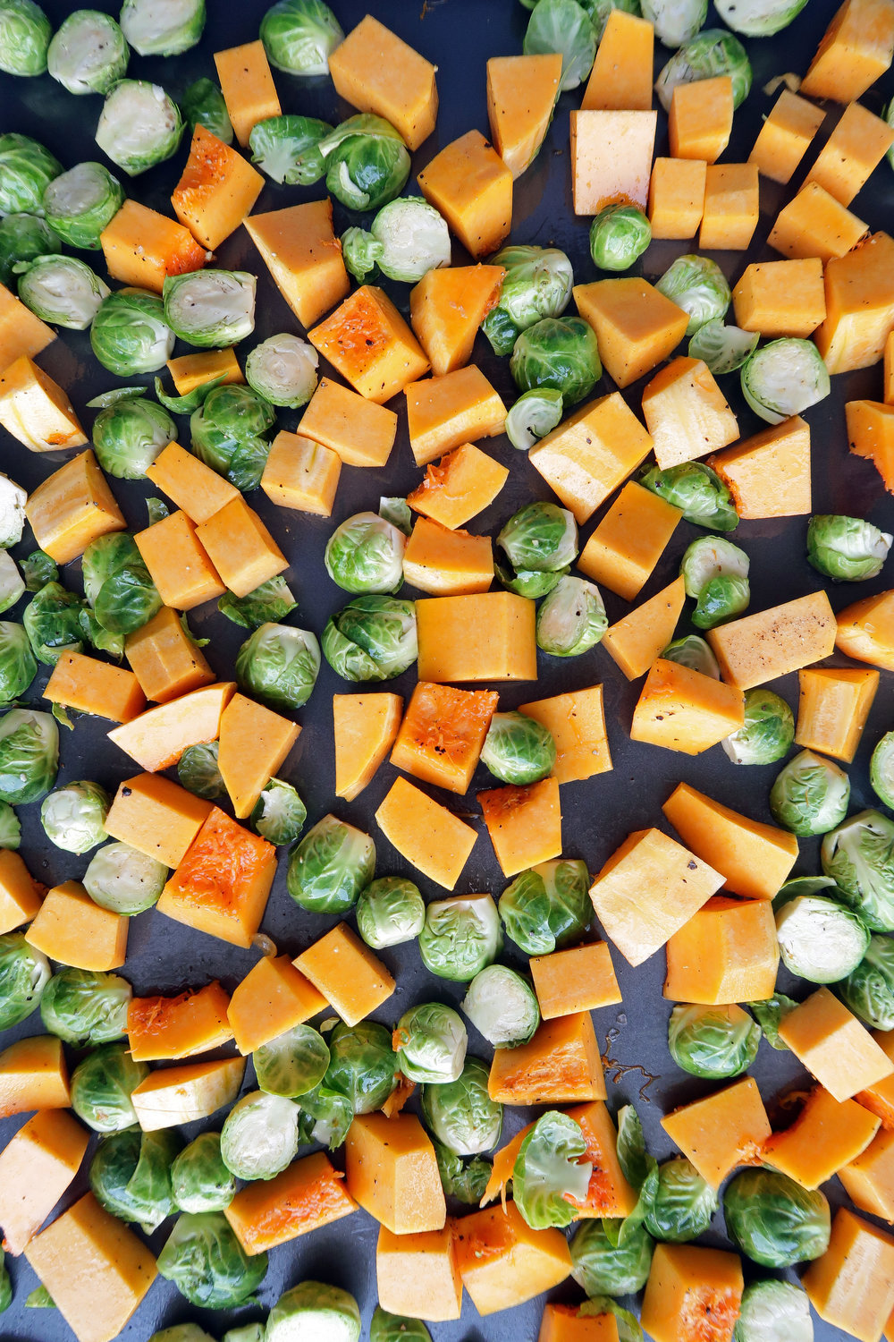 Chopped butternut squash and Brussels in a single layer on a baking sheet.