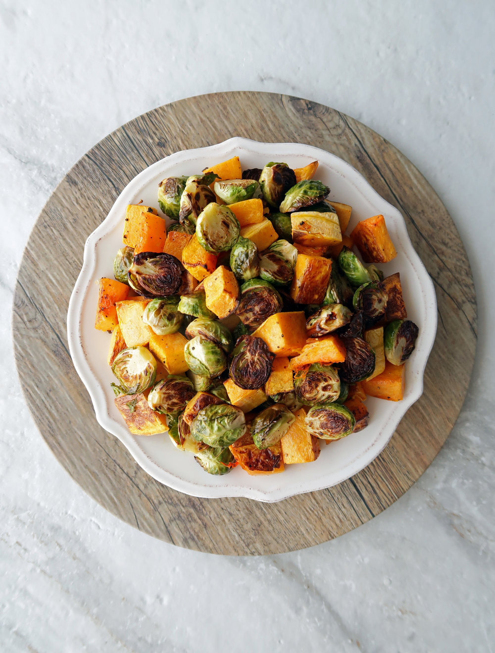 Roasted butternut squash and Brussels sprouts on a white plate.