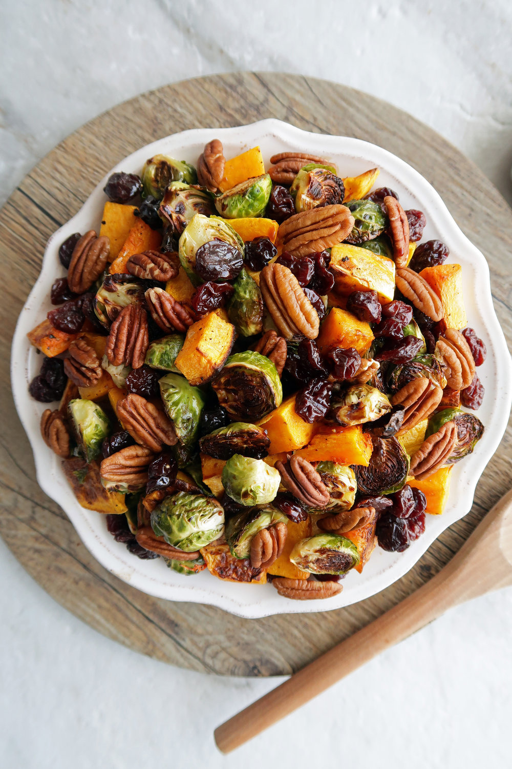 Roasted butternut squash and Brussels sprouts with pecans and dried cherries on a white plate.