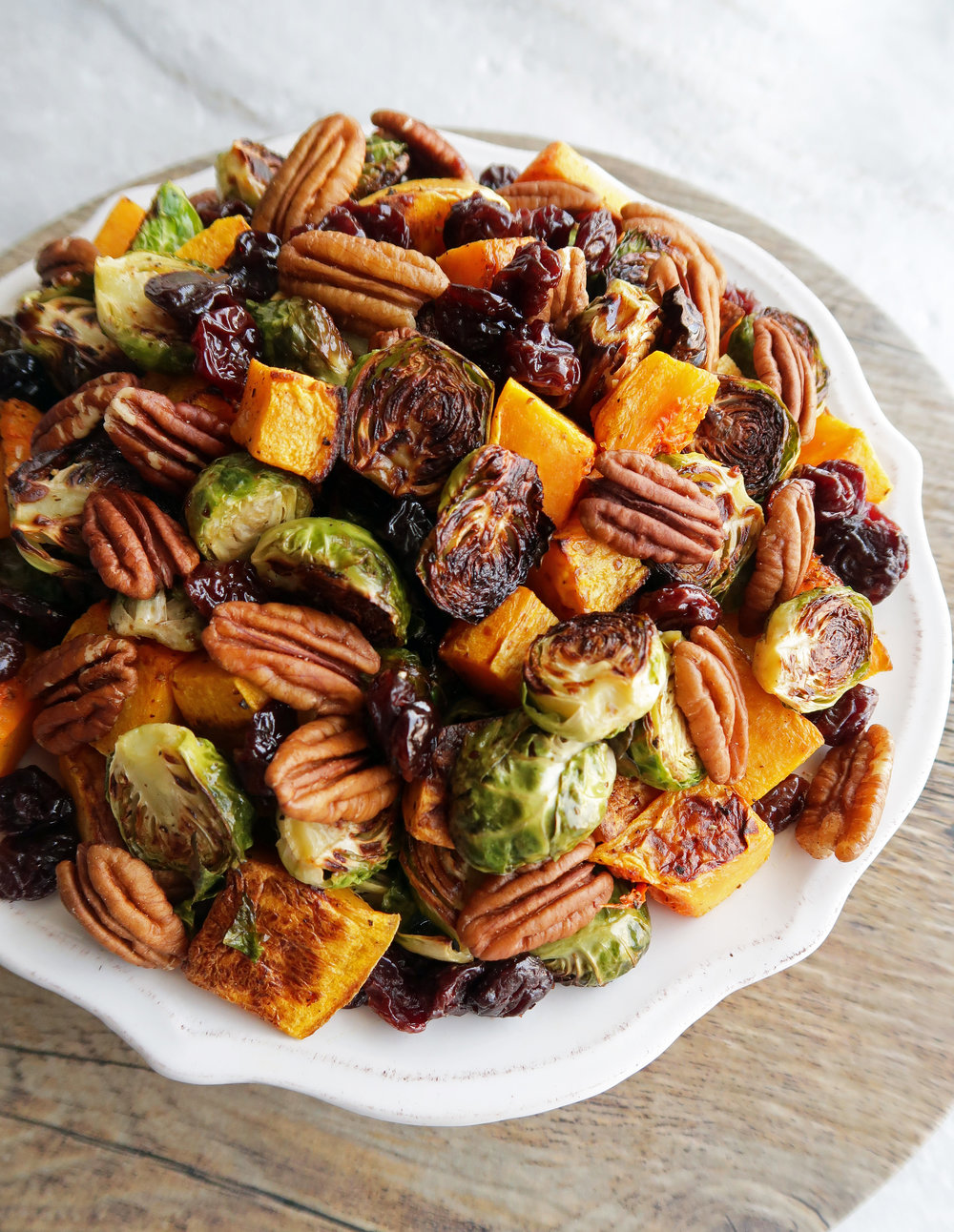 White plate of roasted butternut squash and Brussels sprouts with pecans and dried cherries.