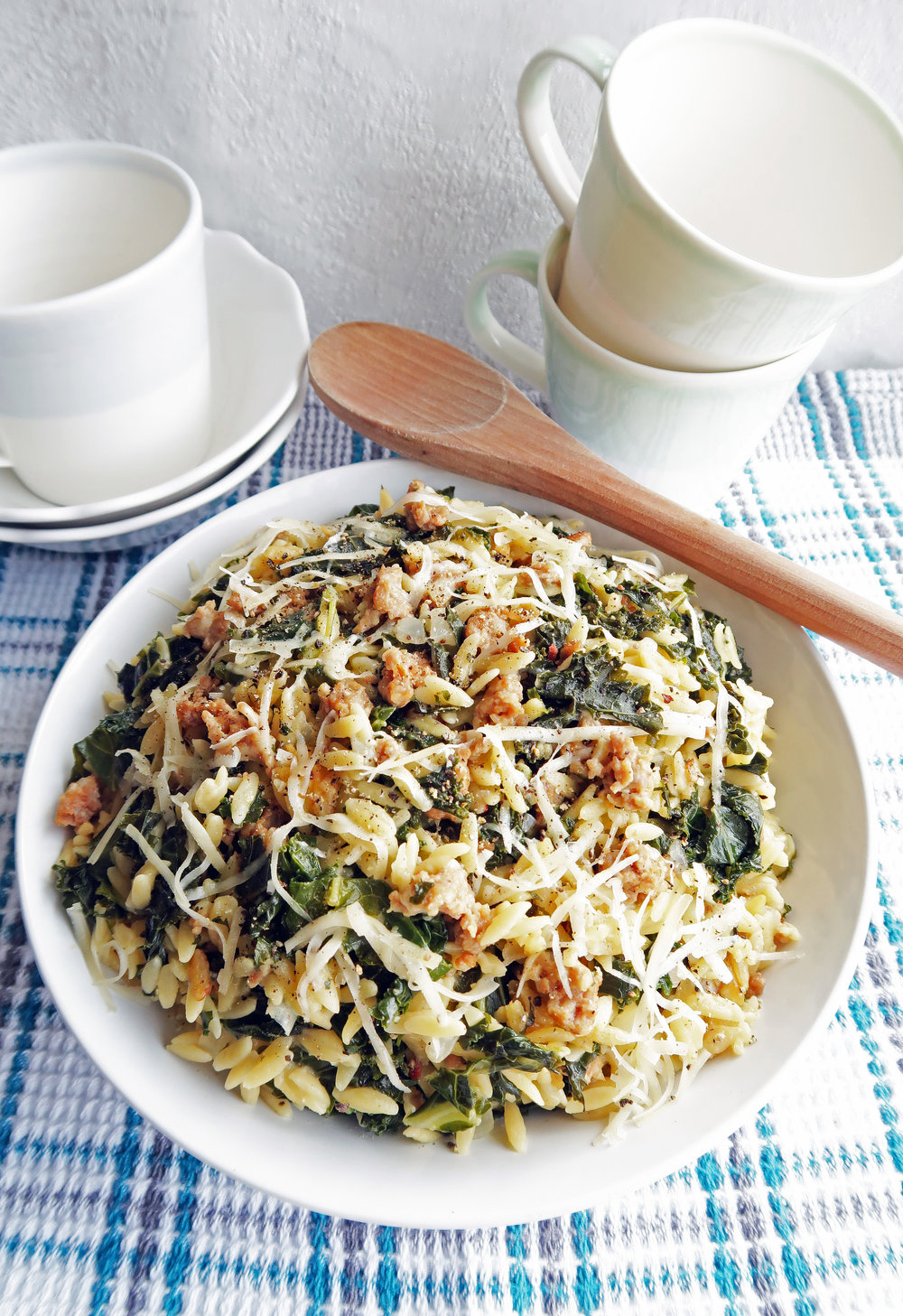 Orzo pasta with Italian sausage and kale with shredded cheese on top in a large pasta bowl.