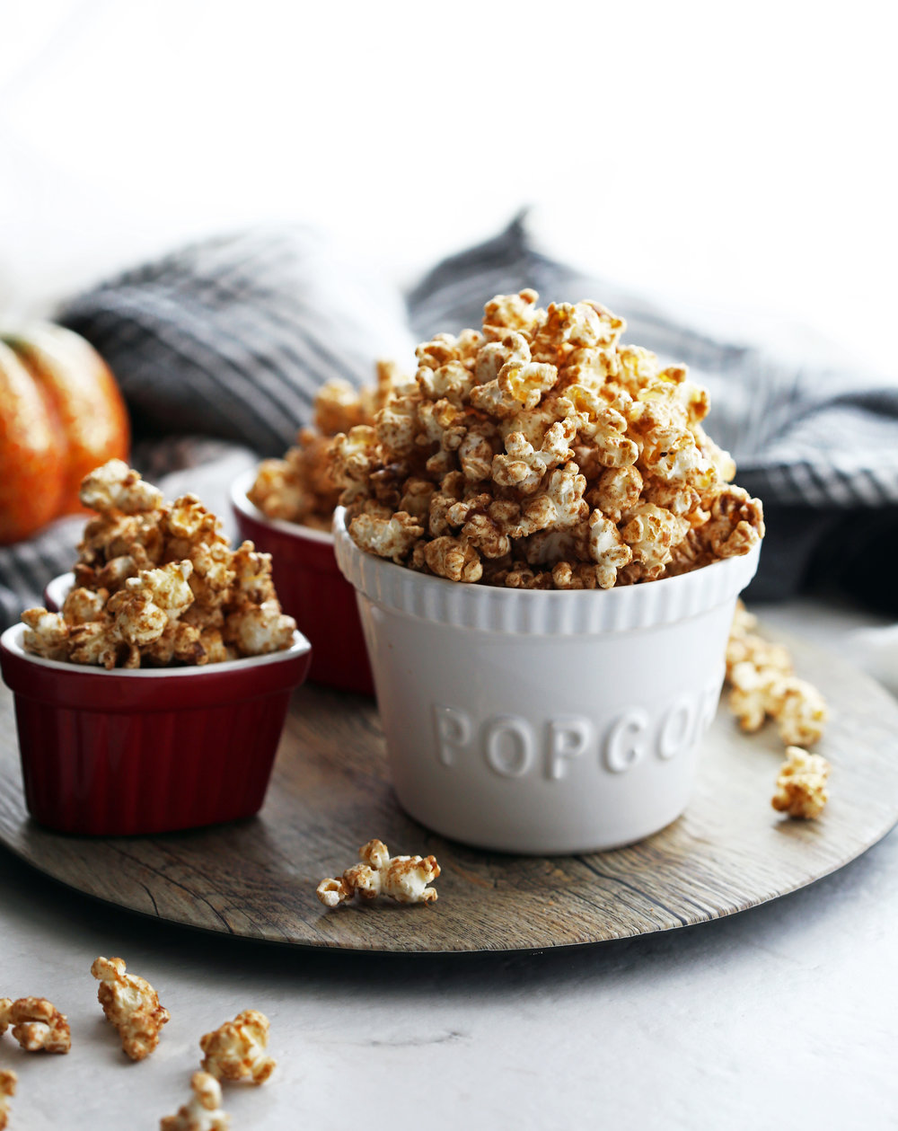 Side view of homemade pumpkin spice butterscotch popcorn in a three bowls with popcorn scattered everywhere.