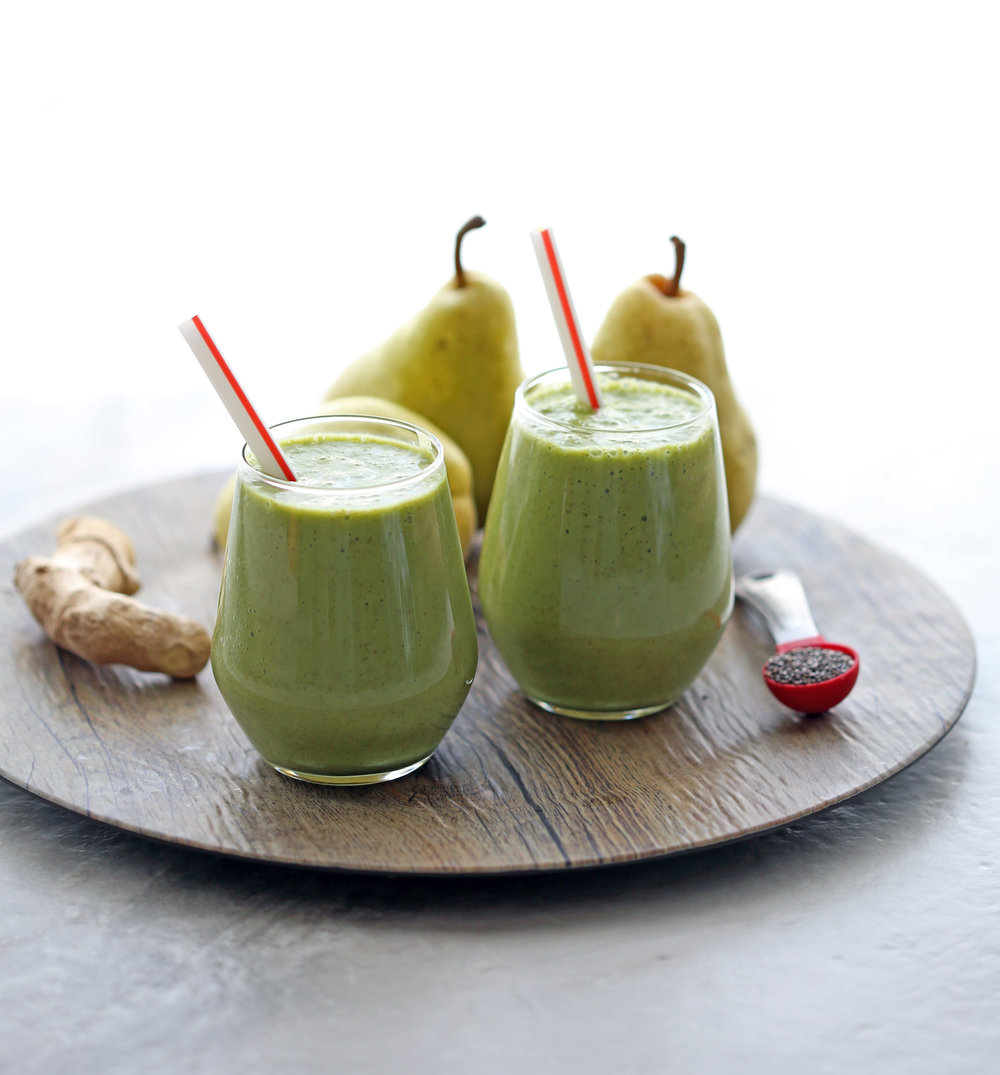 Two glasses of pear ginger chia smoothies with ginger root, pears, and chia seeds around it.