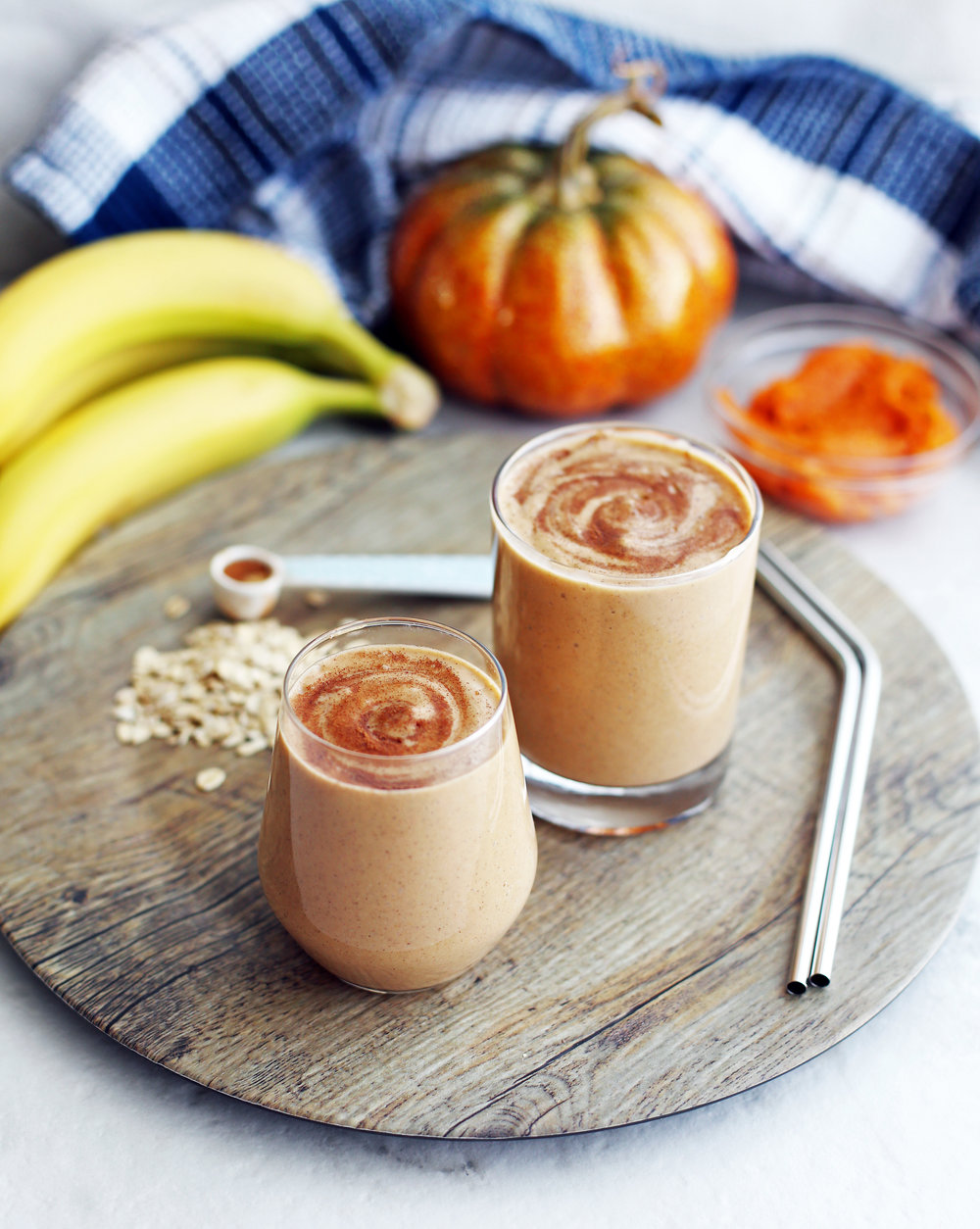 Two glasses of pumpkin pie spice protein smoothies on a round wooden platter.