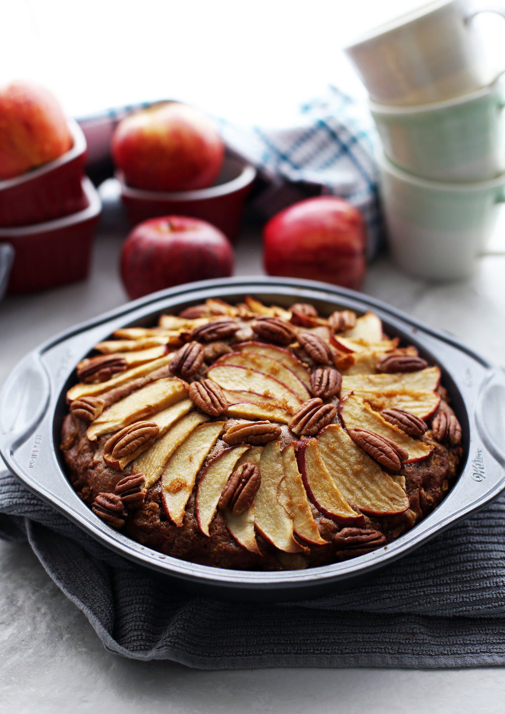 Baked apple cinnamon pecan cake with apple slices and pecans on top in a round cake pan.