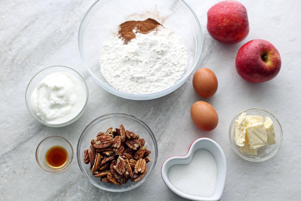 Overhead view of flour mixture, cinnamon, greek yogurt, vanilla extract, pecans, eggs, butter, and apples.