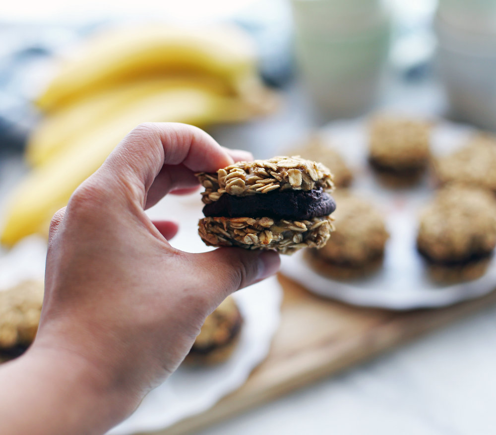 A hand holding a single banana oatmeal sandwich cookies with peanut butter cocoa filling.