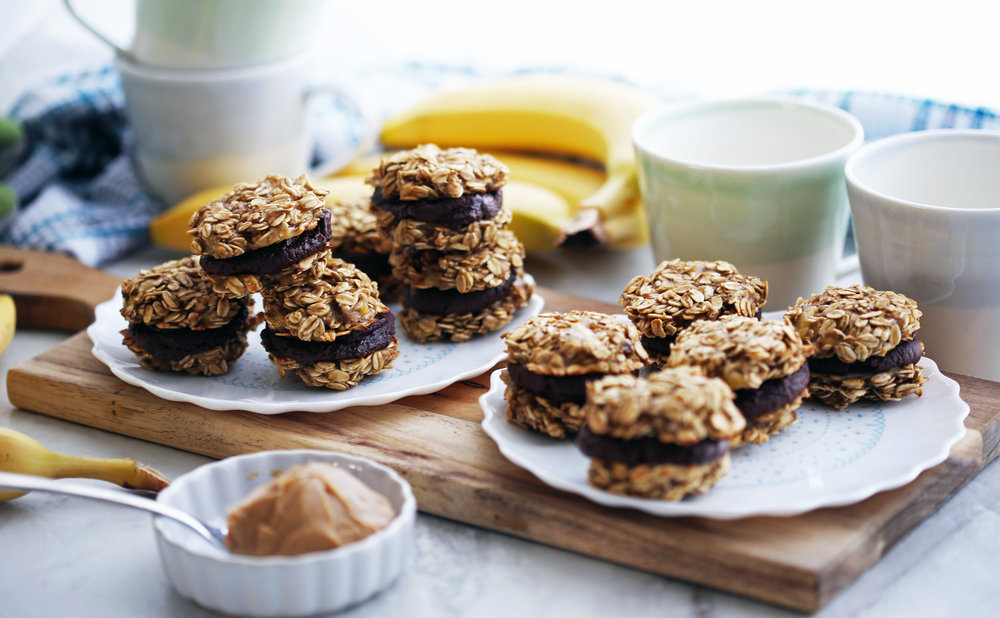 Two plates on a wooden board full of banana oatmeal sandwich cookies with peanut butter cocoa filling.