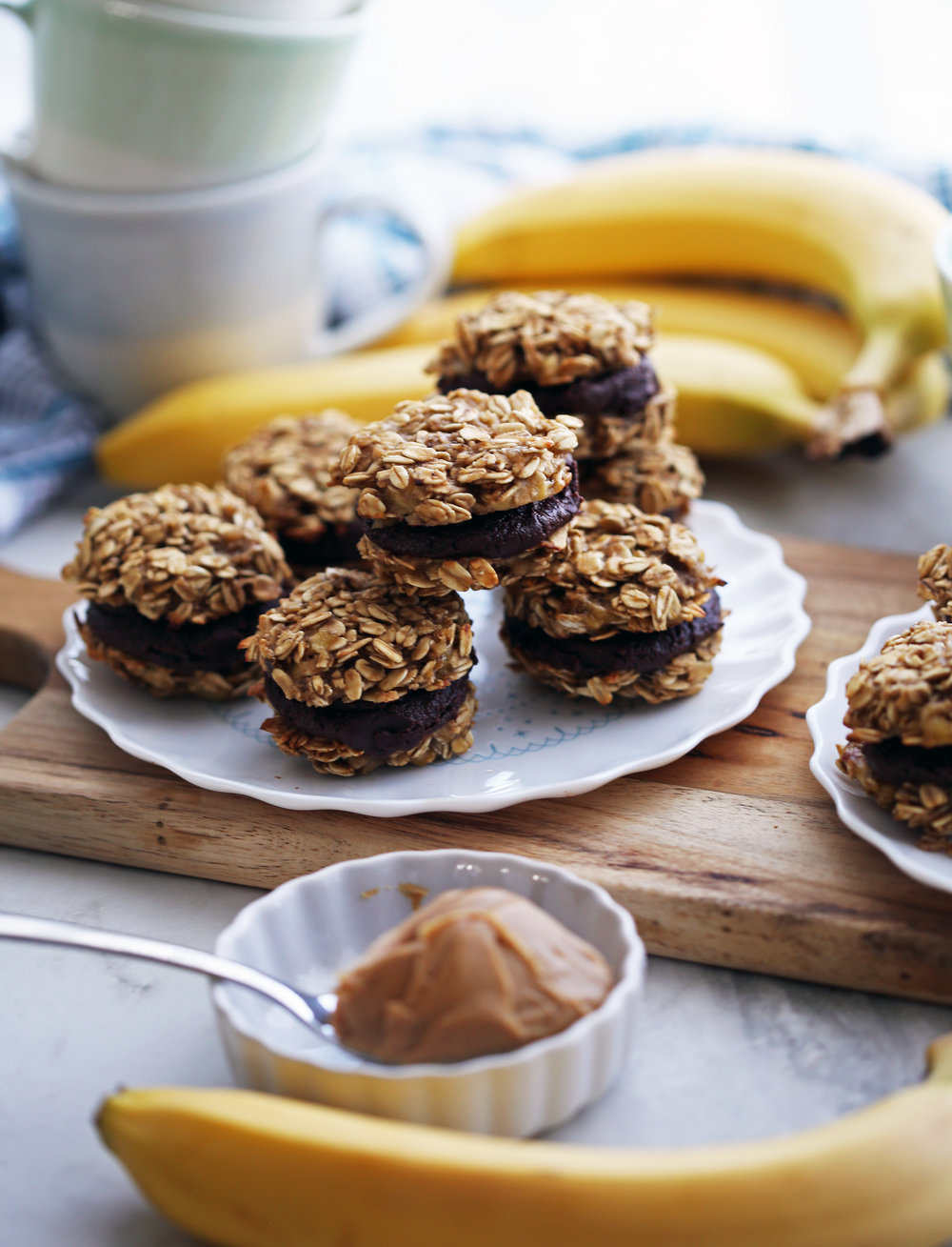 Banana oatmeal sandwich cookies with peanut butter cocoa filling on a white plate.