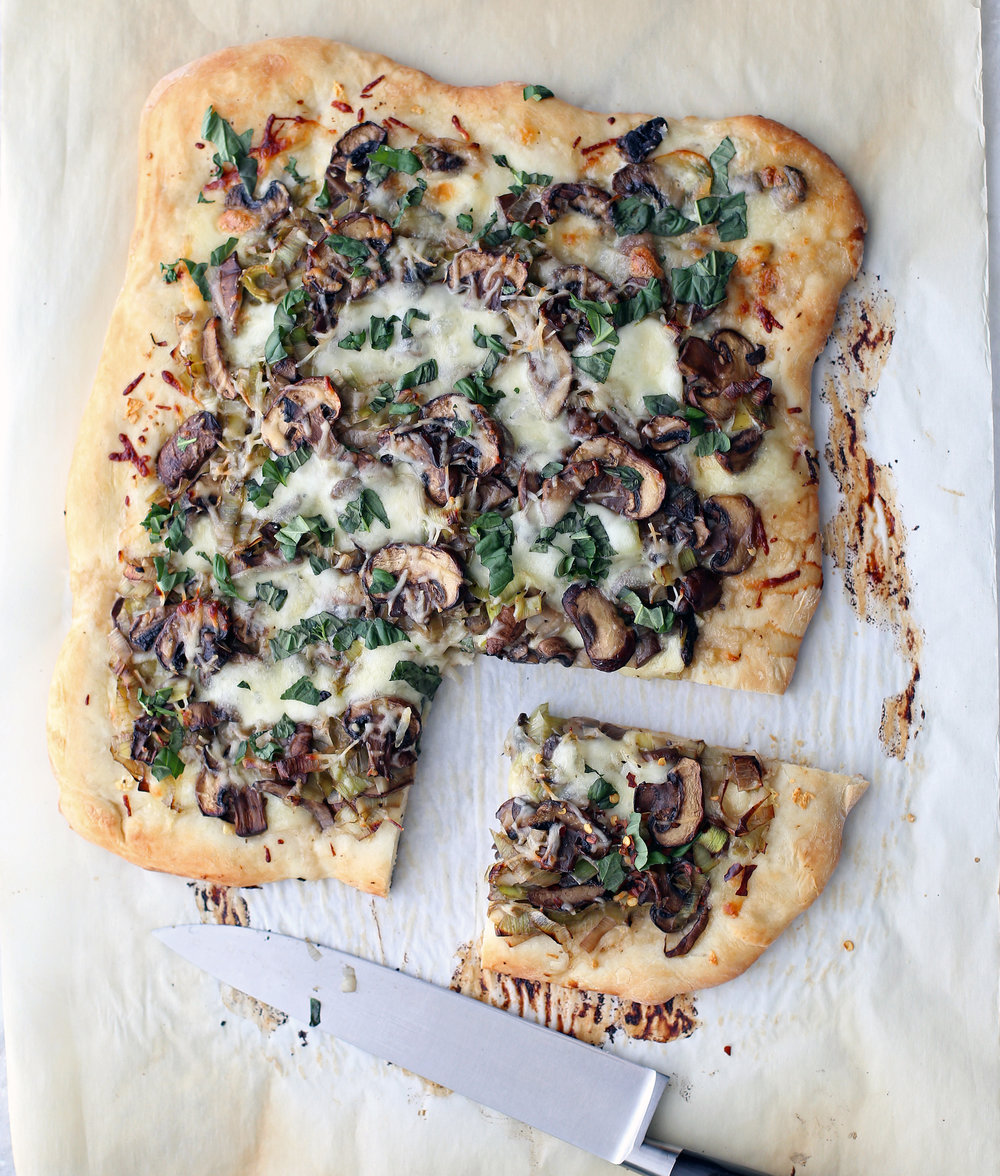 Baked leek mushroom mozzarella pizza with one slice cut on parchment paper.