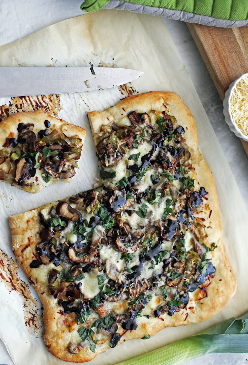 Rustic rectangle leek mushroom mozzerella pizza on parchment paper.
