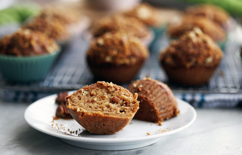 A cinnamon pecan applesauce muffin cut in half on a white plate.