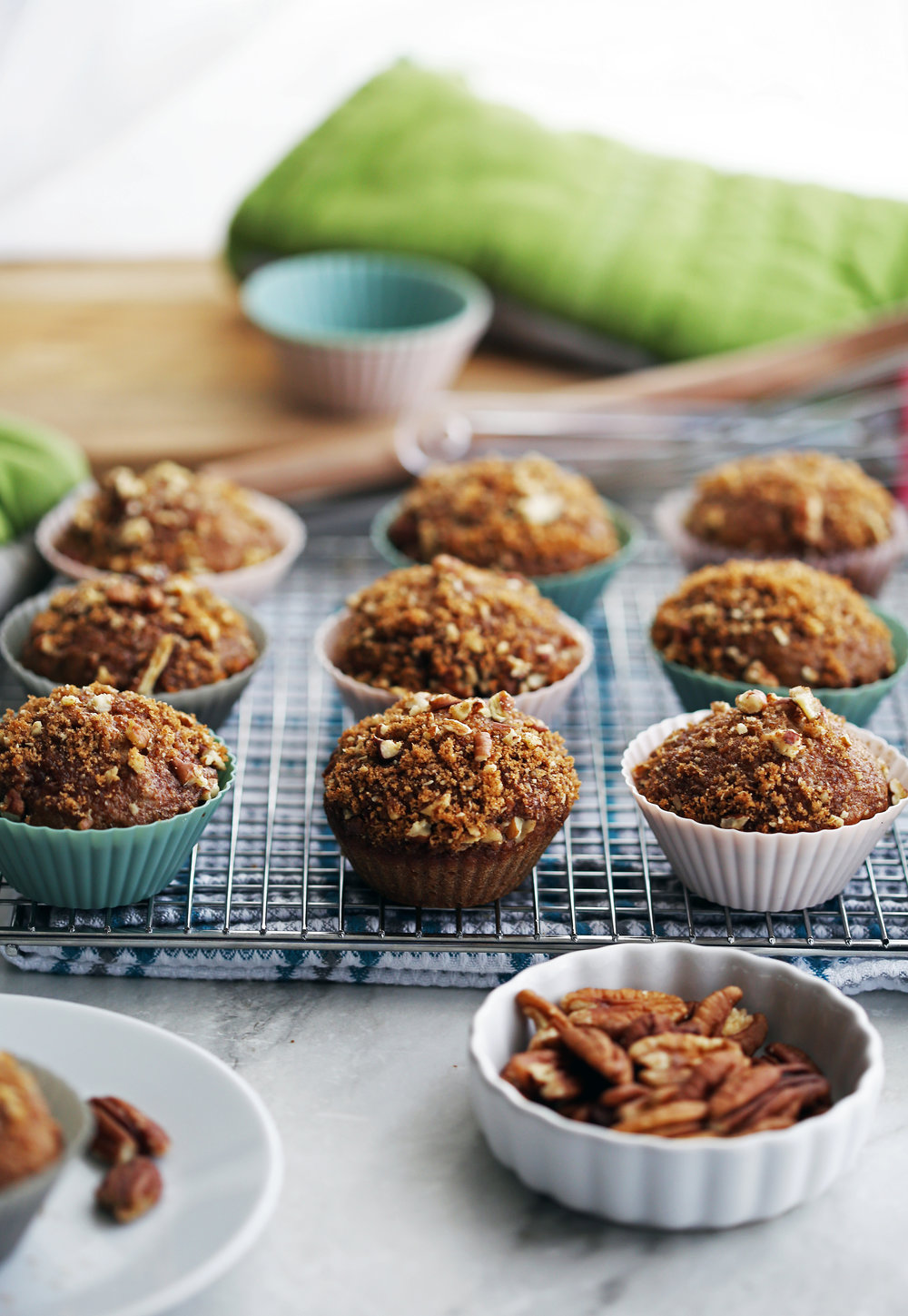 Cinnamon pecan applesauce muffins with a crunchy pecan topping on a cooling rack.