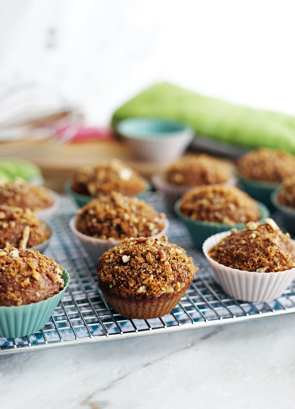 Side view of cinnamon pecan applesauce muffins with a crunchy pecan topping on a cooling rack.