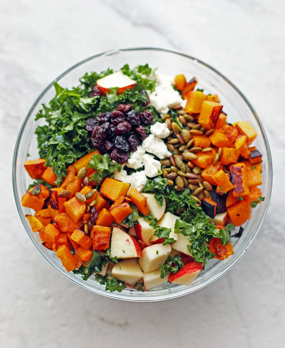 A bowl filled with kale, apples, roasted butternut squash, goat cheese, dried cherries, and pumpkin seeds.