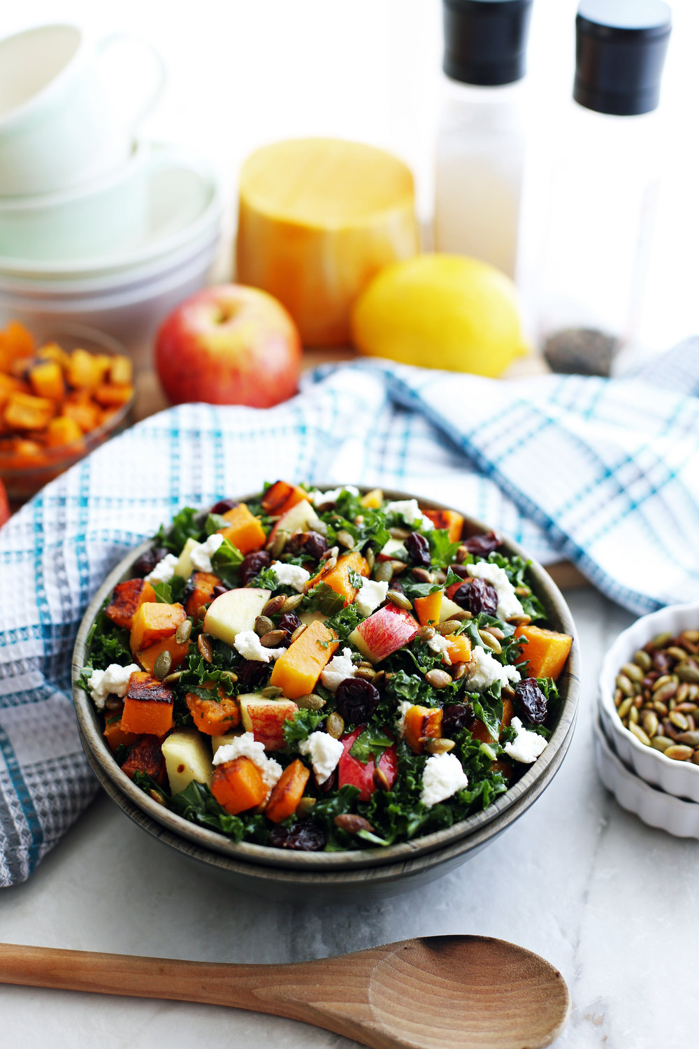 Bowl of kale salad with roasted butternut squash, apple, goat cheese, pumpkin seeds, and dried cherries.