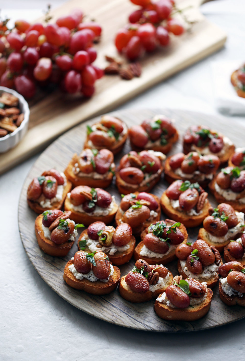 Balsamic roasted grape and goat cheese crostini garnished with fresh mint on a round platter.