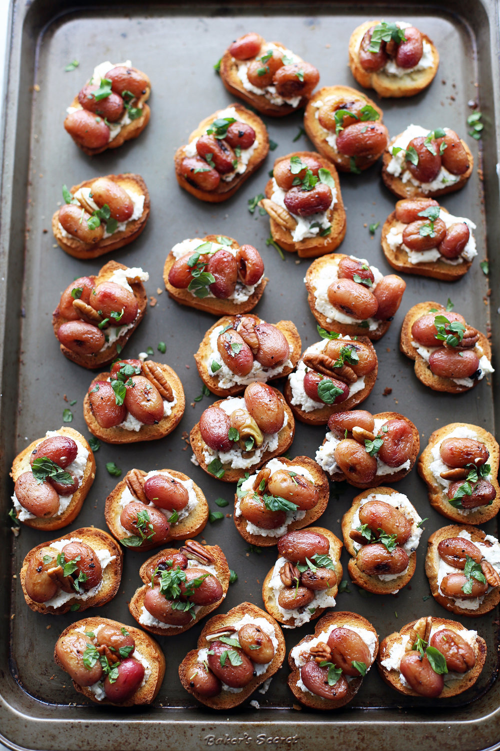 Overhead view of balsamic roasted grape and goat cheese crostini on a baking sheet.
