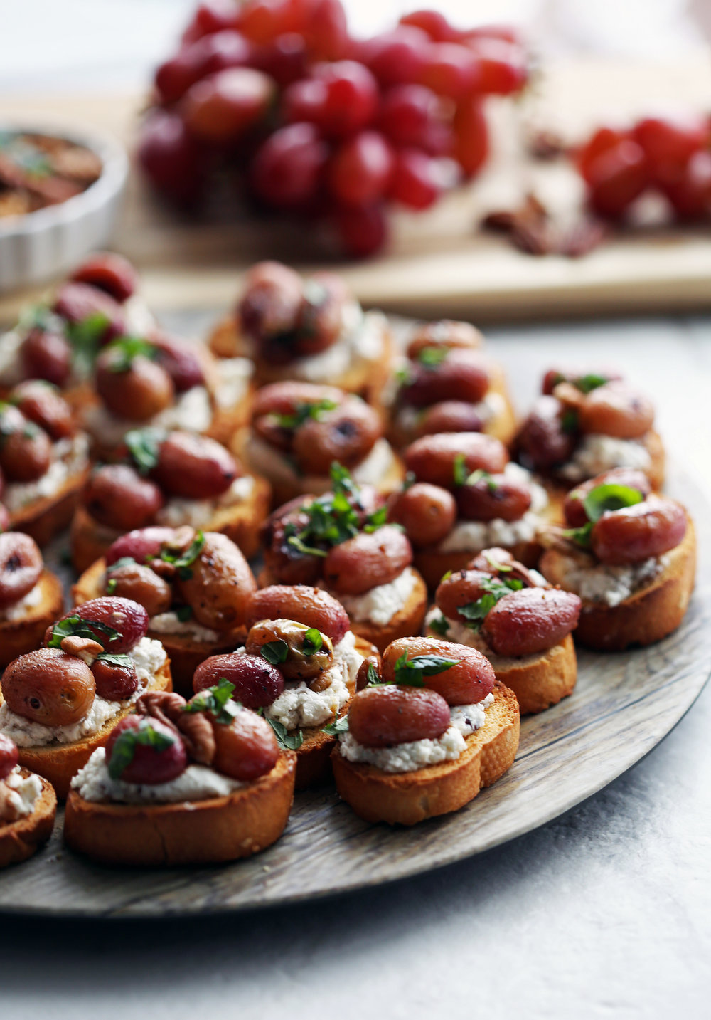 Side view of balsamic roasted grape and goat cheese crostini on a round platter.