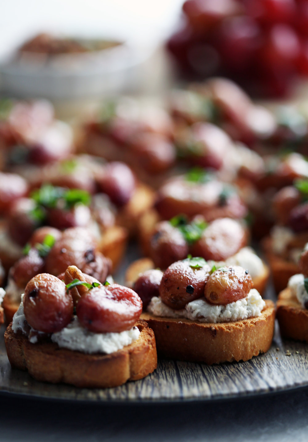 Side close-up of two roasted grape and goat cheese crostini with more crostini in the background.